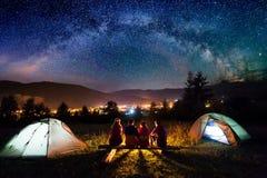 Vriendenwandelaars die naast kamp en tenten in de nacht zitten stock foto's