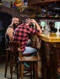 Vriendschap en vrije tijd Vrienden die in bar ontspannen Ordedranken bij barteller Besteedt de Hipster brutale gebaarde mens vrij stock foto's