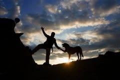 Vriendschap van de hond en de zonsopgang bij de top Royalty-vrije Stock Afbeeldingen