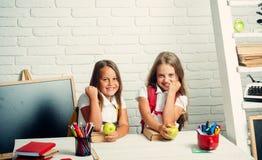 Vriendschap van kleine zusters in klaslokaal bij kennisdag Gelukkige schooljonge geitjes bij les in 1 september De meisjes eten royalty-vrije stock afbeelding