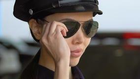 Vriendschappelijk Aziatisch politieagente in op zonnebril zetten en hoed die, vertrouwen glimlachen stock footage