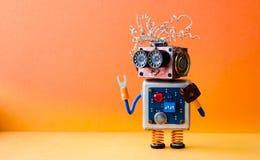 Vriendschappelijk gek robotmanusje van alles op oranje achtergrond Creatief ontwerp cyborg stuk speelgoed Exemplaar ruimtefoto stock fotografie