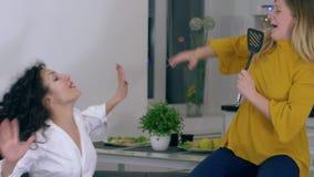 Vriendschappelijk omhels, hebben de vrolijke meisjes pret en zingen in keukenspatel in vrije tijd stock videobeelden