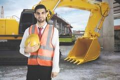 Vriendschappelijke Arabische architect die zich dichtbij een tractor bevinden royalty-vrije stock foto