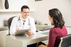 Vriendschappelijke arts die aan een patiënt spreken Royalty-vrije Stock Foto's