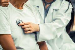 Vriendschappelijke arts die de hogere mens behandelt stock foto's