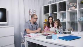 Vriendschappelijke artsenbesprekingen met patiëntenmamma en haar dochter De arts in haar bureau onderzoekt een weinig een keelpij stock footage