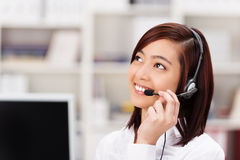 Vriendschappelijke call centreexploitant die op een telefoon babbelen stock afbeelding