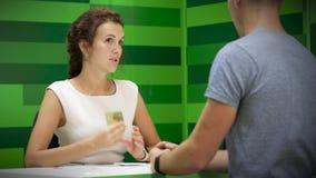 Vriendschappelijke damebankbediende die met cliënt spreken stock videobeelden