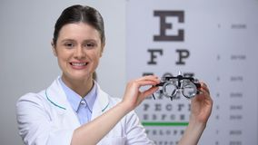 Vriendschappelijke dameopticien die optisch proefkader aan camera, zicht het testen stoppen stock video