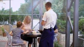 Vriendschappelijke glimlachende kelner die orde nemen bij lijst van familie die diner hebben samen terwijl hun dalingen van het z stock videobeelden