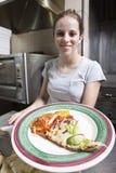 Vriendschappelijke glimlachende serveerster die een plak van pizza dient Stock Afbeeldingen