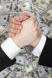 Vriendschappelijke handdruk op de achtergrond van geld Stock Afbeelding