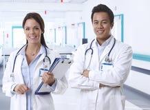 Vriendschappelijke jonge artsen op de glimlach van de het ziekenhuisgang stock afbeelding