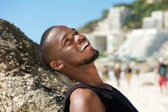 Vriendschappelijke jonge mens die bij het strand glimlachen Stock Foto