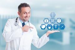 Vriendschappelijke knappe dokter die digitale knopen met medische ico houden Stock Afbeeldingen