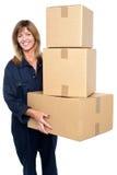 Vriendschappelijke leveringsvrouw met drie ingepakte kartons Stock Afbeelding