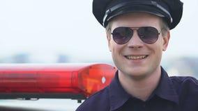 Vriendschappelijke mannelijke politieman die aan camera, vertrouwende op politie, bescherming kijken stock video