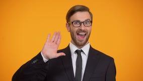 Vriendschappelijke mens die in kostuum golvende hand die, hello, voor het werk, onderwijs uitnodigen zeggen stock footage