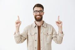 Vriendschappelijke opgetogen en opgewonden knappe grappige donkerbruin met lange baard in glazen en beige jasje die wijsvingers o stock afbeeldingen