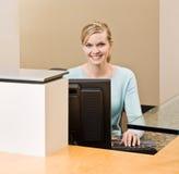 Vriendschappelijke receptionnist die aan computer werkt royalty-vrije stock fotografie