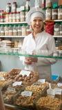 Vriendschappelijke rijpe vrouwelijke verkoper dichtbij zakken van bonenwinkel Royalty-vrije Stock Foto