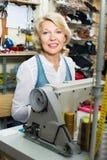 Vriendschappelijke rijpe vrouwenkleermaker die naaimachine met behulp van Royalty-vrije Stock Afbeelding