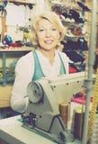 Vriendschappelijke rijpe vrouwenkleermaker die naaimachine met behulp van Royalty-vrije Stock Foto