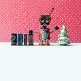 Vriendschappelijke robot 2018 letterzetselcijfers, rood puntpatroon als achtergrond Creatieve Kerstmisaffiche van het ontwerp nie stock afbeeldingen