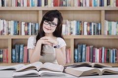 Vriendschappelijke student die in de bibliotheek glimlachen stock afbeelding