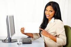 Vriendschappelijke uitvoerende dame die een witte kaart toont Stock Afbeelding