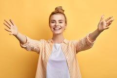 Vriendschappelijke vriendelijke glimlachende vrouw met een open hand klaar voor het koesteren royalty-vrije stock fotografie
