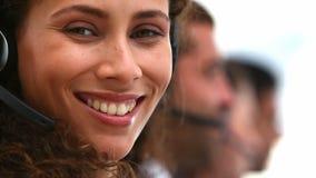 vriendschappelijke vrouw die op een klantenondersteuningsteam glimlachen stock footage
