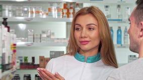 Vriendschappelijke vrouwelijke apotheker die een klant helpen bij de drogisterij stock videobeelden