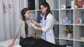 Vriendschappelijke vrouwelijke arts die een meisjestiener in de ruimte in het ziekenhuis onderzoeken De arts luistert aan de adem stock videobeelden