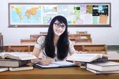 Vriendschappelijke vrouwelijke middelbare schoolstudent die in klasse bestuderen stock afbeeldingen
