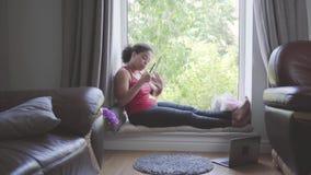 Vrij Afrikaanse Amerikaanse vrouwenzitting op de scherpe spijkers van de venstervensterbank met een nagelvijl Het meisje die om z stock video