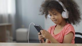 Vrij Afro-Amerikaans kind die oortelefoons dragen en aan muziek op cellphone luisteren stock videobeelden