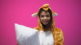 Vrij Afro-Amerikaans meisje die in girafpyjama's hoofdkussen houden, die op camera kijken stock video