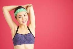 Vrij Aziatisch meisje die terwijl het doen van aerobics en yoga in a uitrekken zich Stock Foto's