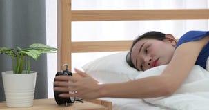 Vrij Aziatische vrouw die omhoog het liggen op haar bed weigeren te wekken stock videobeelden