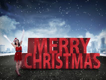 Vrij Aziatische vrouw die zich met vrolijke Kerstmis 3D teksten bevinden Royalty-vrije Stock Foto's