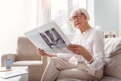 Vrij bejaarde dame die een krant in woonkamer lezen stock fotografie