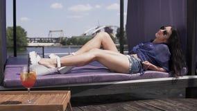 Vrij blij meisje met donker lang haar en lange naakte benen die in de zon die op een lanterfanter rusten liggen Vrouw in zonnebri stock footage
