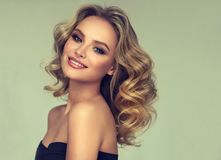 Vrij blond-haired model met krullend, los kapsel en aantrekkelijke make-up stock foto's