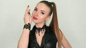 Vrij blond meisje in een zwarte leerkleding met kostbare juwelen stock video