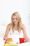 Vrij blonde genietend van ontbijt in bed Stock Fotografie