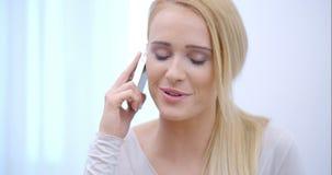 Vrij blonde vrouw die aan een mobiele vraag luisteren stock footage