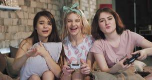 Vrij charismatische dames die van de tijd genieten samen bij sleepovernacht het spelen op een PlayStation-zeer enthousiast spel stock video