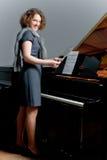 Vrij donker haired jong meisje dat zich dichtbij piano bevindt stock afbeelding